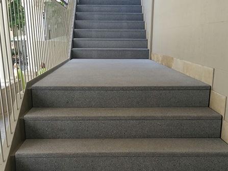 Rehabilitación en piedra artificial de peldaños y rellano